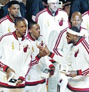 Jugadores de los Heat de Miami muestran su anillos de campeones entregados anoche previo al partido de apertura ante Chicago Bulls