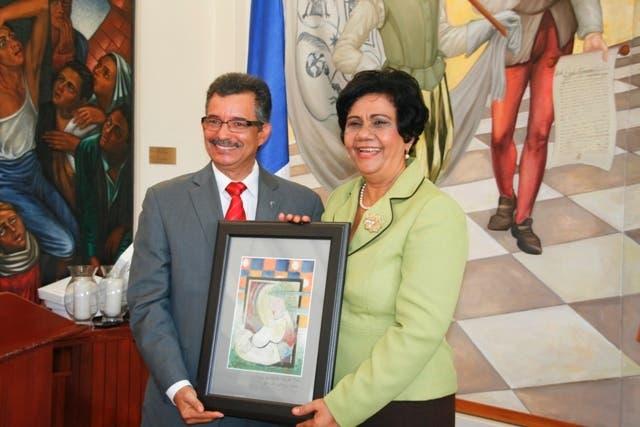 La decana de la facultad de Ciencias de la Educación, Dra. Carmen Evarista Matías, recibe una placa de reconocimiento de manos del vicedecano de Artes, Luis Alberto Rodríguez.
