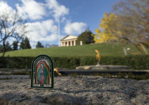 Una pequeña imagen de la Virgen María se sienta en la piedra que rodea la llama eterna tumba del presidente John F. Kennedy, Martes, 19 de noviembre 2013. FOTO AP