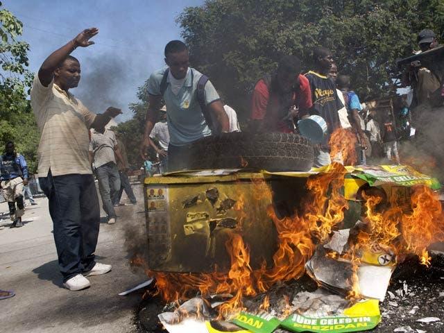 Manifestante quema cartel con fotografía del presidente Haitiano Michelle Martelly durante la protesta realizada ayer lunes en Puerto Principe.  AP