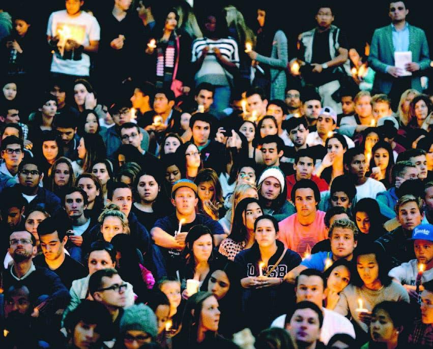 Jóvenes sostienen velas durante una vigilia por la víctimas en la Universidad de California
