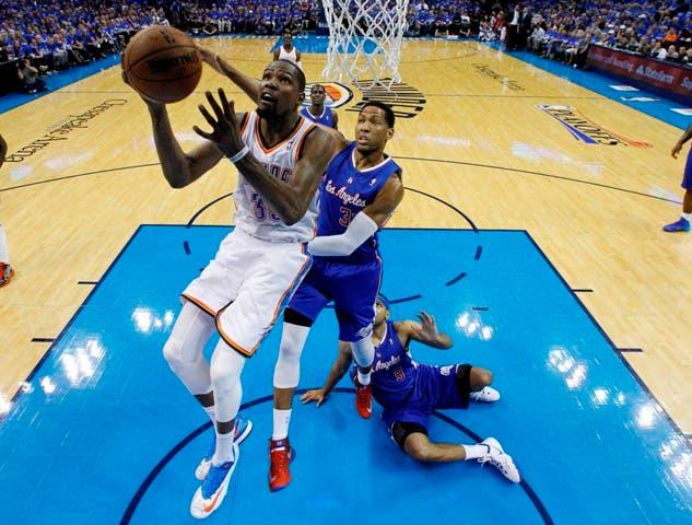 El jugador del Thunder de Oklahoma City, Kevin Durant, izquierda, realiza un tiro contra los Clippers de Los Angeles el lunes, 5 de mayo de 2014, en Oklahoma City. (AP Photo/Sue Ogrocki)