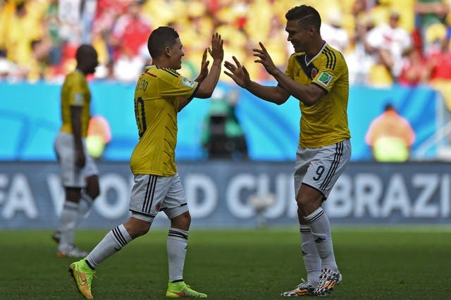 Colombia's midfielder Juan Fernando Quintero (L) celebrates with forward Teofilo Gutierrez after scoring his team's second goal during the Group C football match between Colombia and Ivory Coast at the Mane Garrincha National Stadium in Brasilia during the 2014 FIFA World Cup on June 19, 2014.  AFP PHOTO / EITAN ABRAMOVICH
