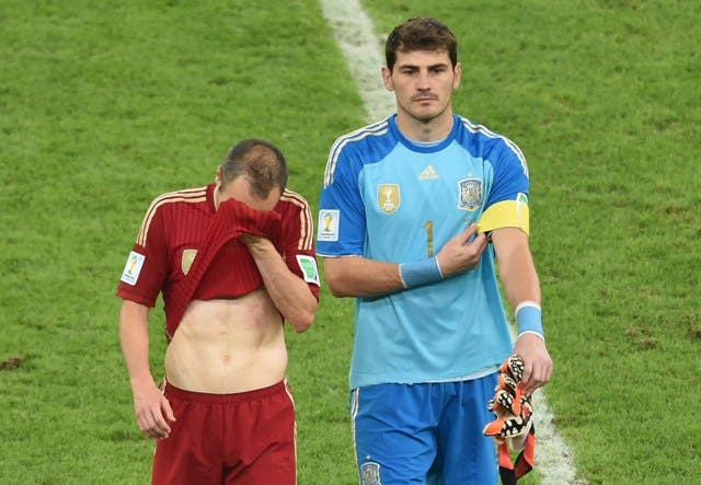 Spain's goalkeeper and captain Iker Casillas (R) and Spain's midfielder Andres Iniesta walk off the pitch after losing their Group B football match against Chile in the Maracana Stadium in Rio de Janeiro during the 2014 FIFA World Cup on June 18, 2014. AFP PHOTO / YASUYOSHI CHIBA