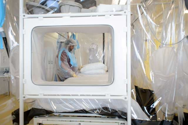 (FILES )- A picture dated August 6, 2014 shows a nurse wearing protective clothing as he demonstrates the facilities in place at the Royal Free Hospital in north London, in preparation for any patients testing positive for the Ebola virus. A British healthcare worker who contracted the Ebola virus in Sierra Leone is being flown to London for treatment, the Department of Health said on August 24, 2014. AFP PHOTO/Leon Neal