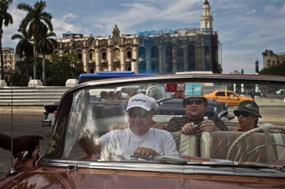 Turistas sentados en un viejo automóvil estadounidense en La Habana Vieja, Cuba, el viernes 26 de septiembre de 2014.FRANKLIN REYES/FOTO AP.