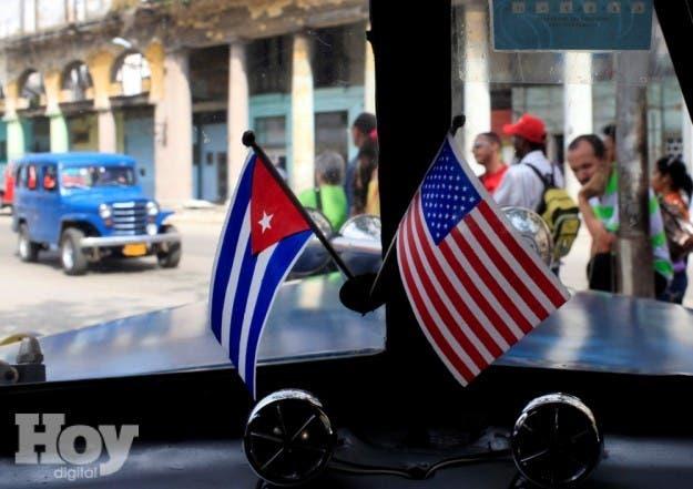 Fotografía de archivo del 22 de marzo de 2013 de dos pequeñas banderas de Cuba y Estados Unidos sobre el tablero de instrumentos de un automóvil en La Habana, Cuba.