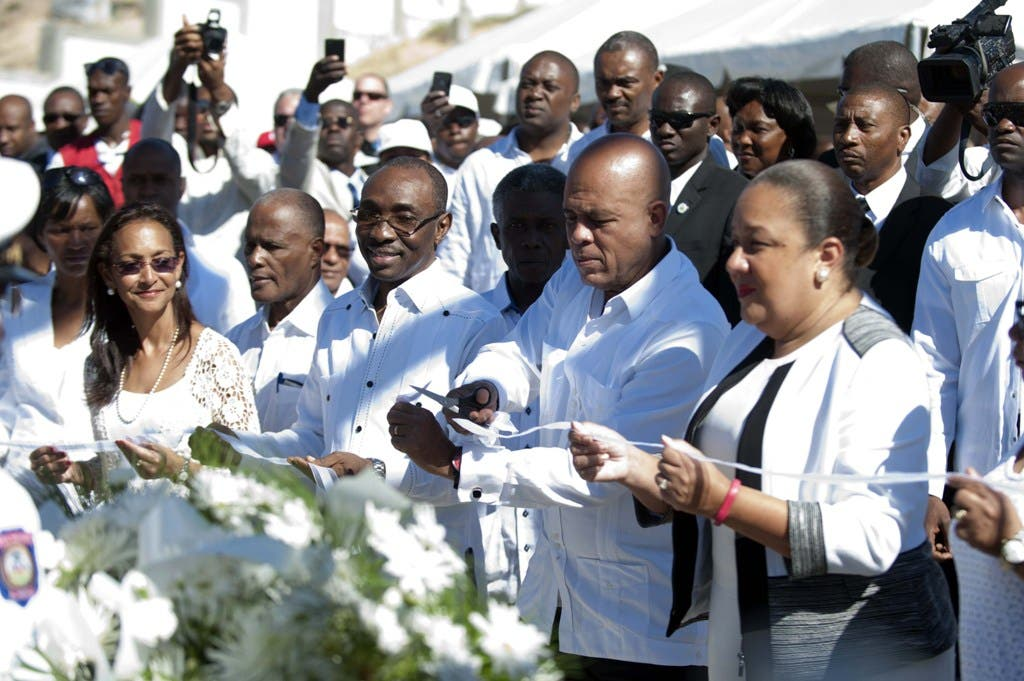 Haitian President Michel Martelly(C), Haitian First Lady Sophia Martelly(R) and Evans Paul, Prime Minister(L) cut a ribbon during a memorial ceremony in honor of the victims of earthquake that hit Haiti in January 12, 2010. Haiti marks the fifth anniversary of a catastrophic earthquake that killed 300,000 people. Port-au-Prince, on January 12, 2015. AFP PHOTO/Hector RETAMAL