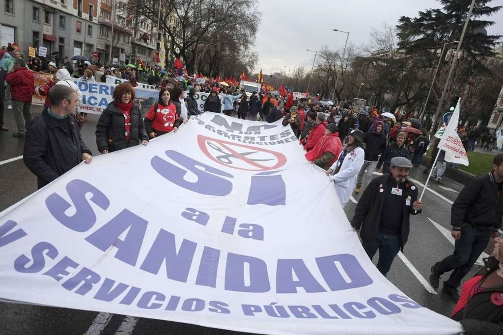 """Demonstrators hold a banner against social cuts and in favour of public health during an anti-austerity demonstration dubbed """"the Marches for Dignity 22-M"""" in Madrid on March 21, 2015. Tens of thousands of people from all over Spain rallied today in Madrid, many of them after several days march to demand """"Bread, work, housing and dignity"""" on the eve of regional elections in Andalusia considered a test to social unrest.  AFP PHOTO / PEDRO ARMESTRE"""