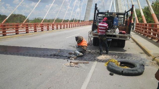 Técnicos proceden a dar mantenimiento a una de las juntas del puente Mauricio Báez, sobre el río Higuamo.