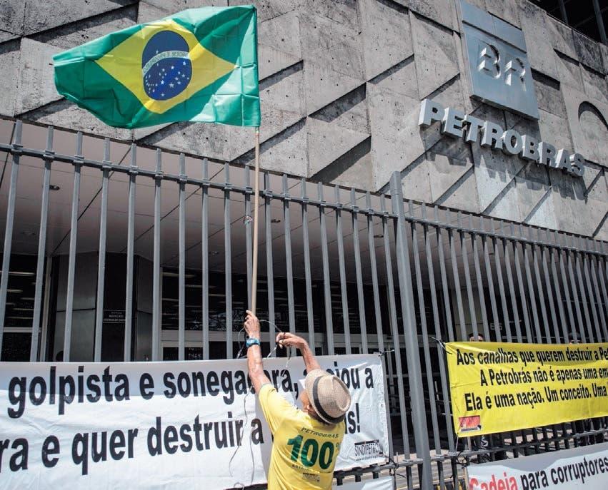 Un obrero ata una bandera a la verja de la sede de Petrobras durante una protesta de empleados.