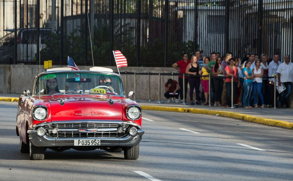 A vintage car with US flags drives by the US embassy in Havana, on July 20, 2015. The United States and Cuba formally resumed diplomatic relations Monday, as the Cuban flag was raised at the US State Department in a historic gesture toward ending decades of hostility between the Cold war foes.  AFP PHOTO/ADALBERTO ROQUE