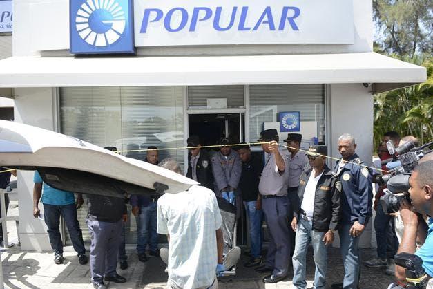 Agentes del DICRIM retiran el cadáver del vigilante asesinado en oficina Banco  Popular de Las Praderas.   Arismendy Lora