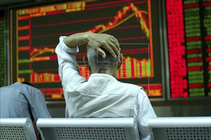 Un inversor revisa una pantalla con información bursátil en Pekín (China). EFE/Archivo