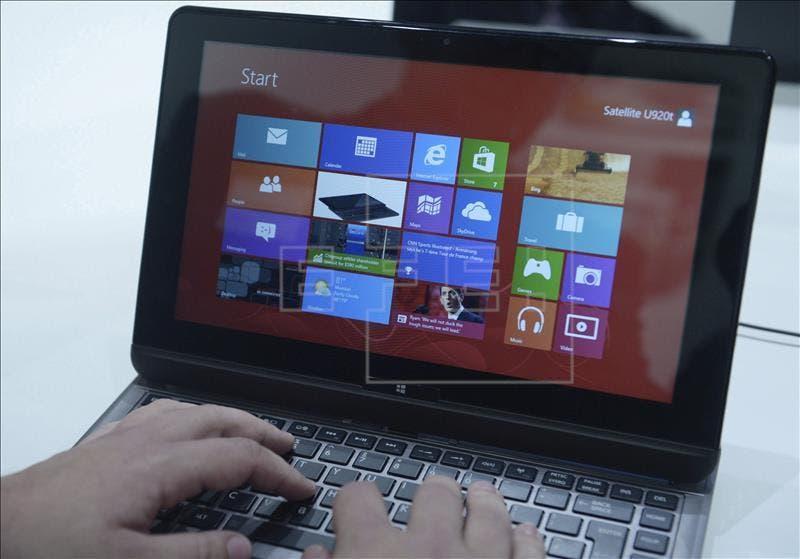 """Un expositor opera con el sistema operativo """"Windows 8"""" instalado en un terminal híbrido de ordenador portátil. EFE/Archivo"""