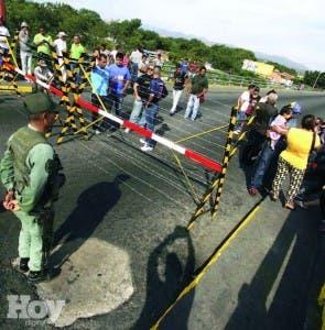 Colombianos esperan poder cruzar frontera con Venezuela, custodiada por militares.  AFP