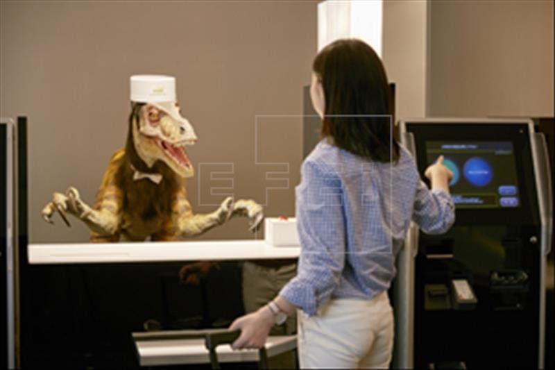 """En la imagen el velocirraptor robot recepcionista atiende a una cliente del hotel que hace el """"check-in"""" a través de una máquina. Foto: cedida por Henn Na Hotel/Huis Ten Bosch"""