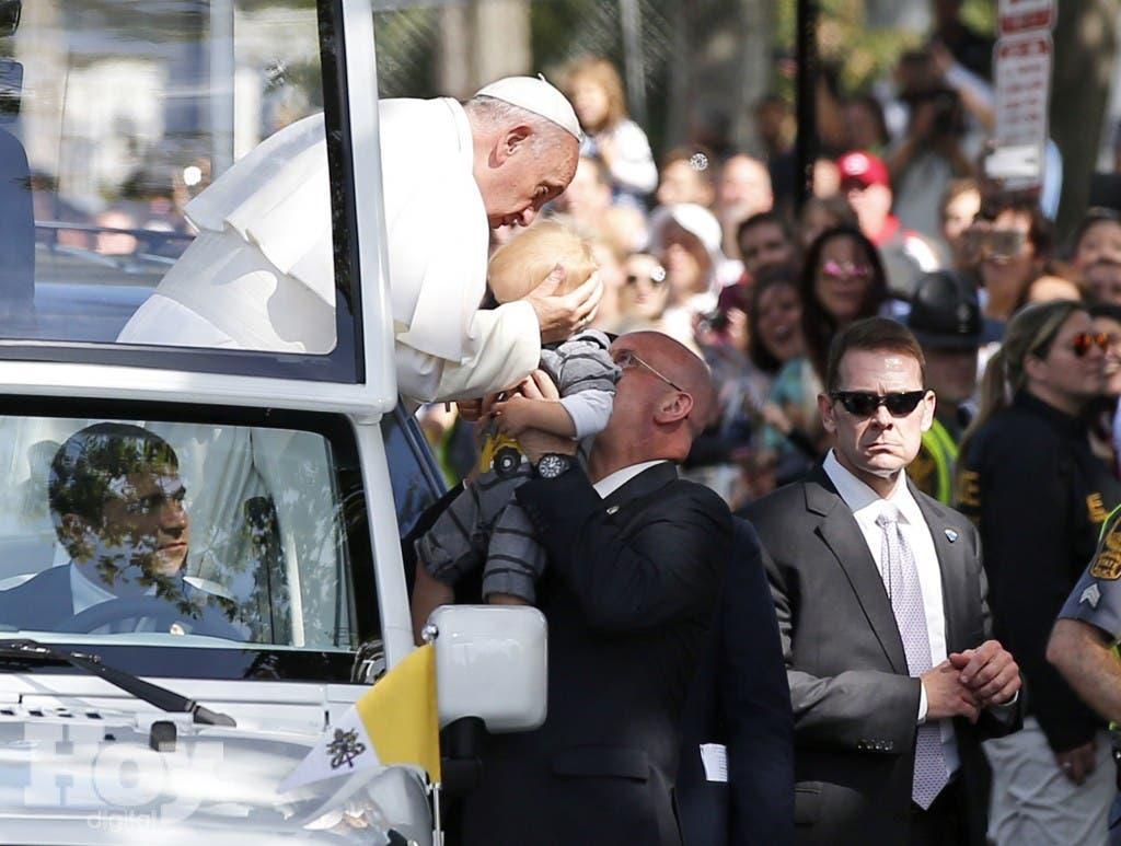 Papa Francisco besa a un bebé durante su recorrida por las calles de Washington en el papamóvil, miércoles 23 de septiembre de 2015. (AP Foto/Alex Brandon, Pool)