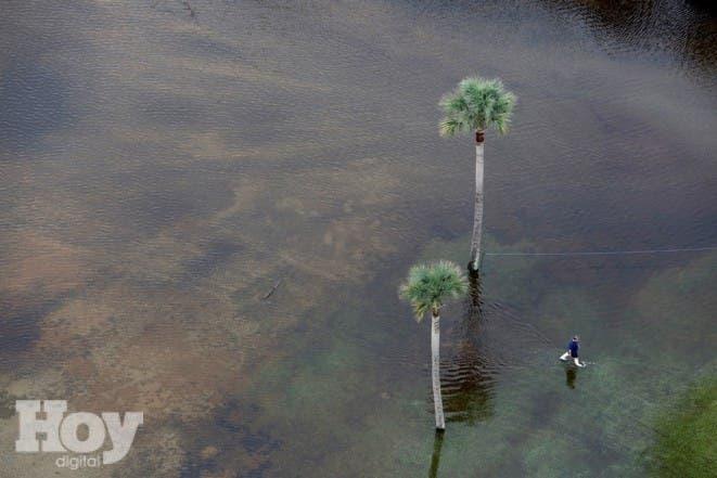 Un hombre camina por aguas inundadas en el aparcamiento de The Citadel Beach Club en Isle of Palms, South Carolina, el lunes 5 de octubre de 2015. Charleston y sus alrededores siguen luchando con las inundaciones debido a una tormenta que se desplaza a baja velocidad. (AP Foto/Mic Smith)