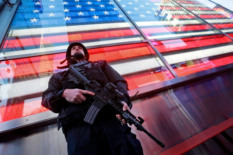 "A heavily armed New York city police officer with the Strategic Response Group stands guard at the armed forces recruiting center in New York's Times Square, Saturday, Nov. 14, 2015.  Police in New York say they've deployed extra units to crowded areas of the city ""out of an abundance of caution"" in the wake of the attacks in Paris, France. A New York Police Department statement released Friday stressed police have ""no indication that the attack has any nexus to New York City."" (AP Photo/Mary Altaffer)"