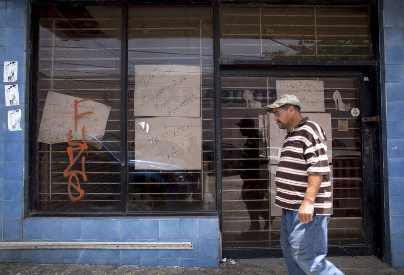 """A man walks past a closed store with signs reading """"Closing down sale"""" and """"Everything goes, shoes, clothes, take advantage"""" in Arecibo, Puerto Rico, June 29, 2015. REUTERS/Alvin Baez-Hernandez"""