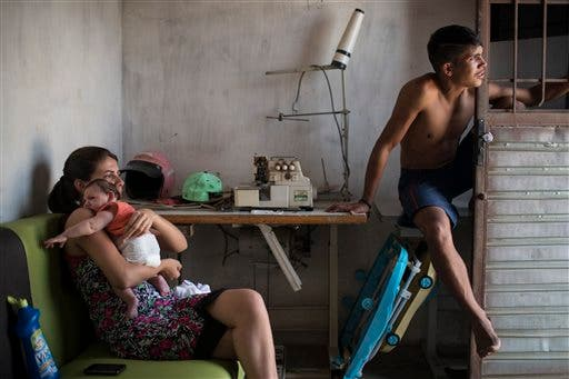 In this Dec. 23, 2015 photo, Angelica Pereira, left, holds her daughter Luiza as she sits with her husband Dejailson Arruda at their home in Santa Cruz do Capibaribe, Pernambuco state, Brazil. Luiza was born in October with a rare condition, known as microcephaly. A neurologist soon gave more bad news: the damage to Luiza's brain had caused cerebral palsy. (AP Photo/Felipe Dana)