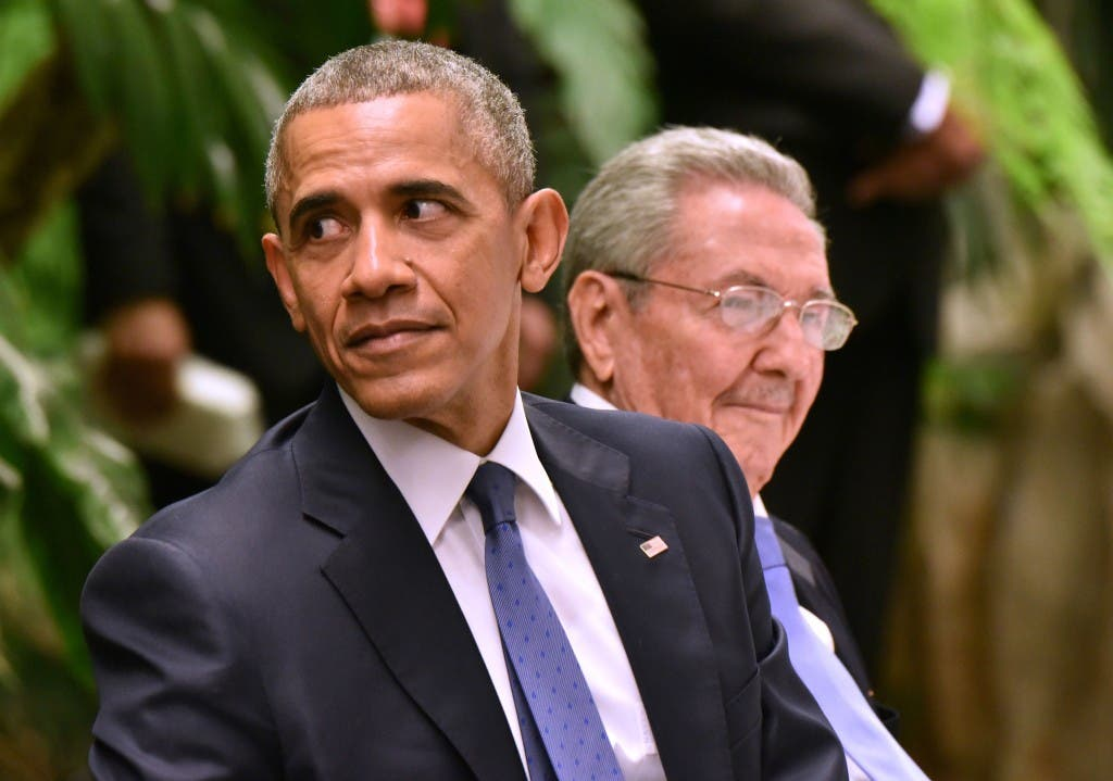 """TOPSHOT - Sitting next to Cuban President Raul Castro (R), US President Barack Obama (L) gestures during the state dinner at the Revolution Palace in Havana on March 21, 2016. Obama and Castro vowed Monday in Havana to set aside their differences in pursuit of what the US president called a """"new day"""" for the long bitterly divided neighbors.    AFP PHOTO/Adalberto Roque / AFP / ADALBERTO ROQUE"""