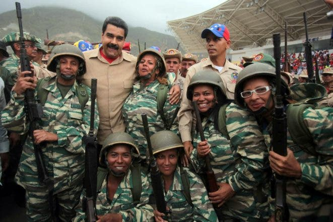 Venezuelan President Nicolas Maduro embraces members of the Bolivarian militia during a military training in Caracas on May 21, 2016. Maduro imposed a state of emergency earlier this week and ordered the two-day war games to show that the military can tackle domestic and foreign threats he says are being fomented with US help. / AFP / Francisco Batista
