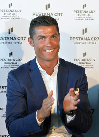"""Portuguese forward Cristiano Ronaldo smiles as he attends the opening of the Pestana CR7 Hotel in Funchal, on Madeira island on July 22, 2016.  Cristiano Ronaldo invested over 37 million euros in the Pestana Hotel group to create four new hotels with the """"CR7"""" logo in Portugal (Lisbon and Funchal), Madrid and New York.  / AFP / JOANA SOUSA"""