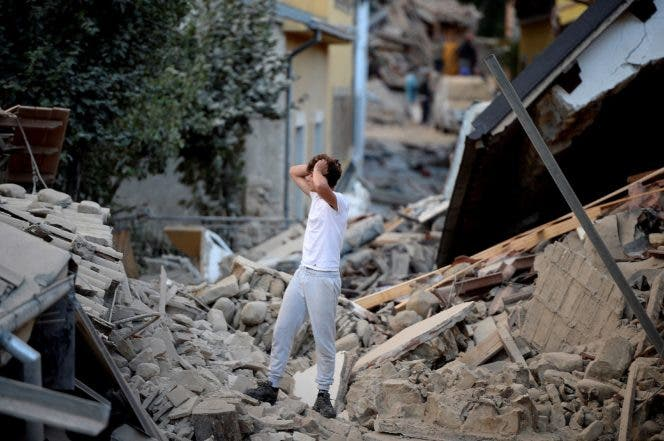 TOPSHOT - A man stands among damaged buildings after a strong earthquake hit central Italy, in Amatrice on August 24, 2016.  A powerful 6.2-magnitude earthquake devastated mountain villages in central Italy on August 24, 2016, left 38 people dead and the total is likely to rise, the country's civil protection unit said in the first official death toll. Scores of buildings were reduced to dusty piles of masonry in communities close to the epicentre of the pre-dawn quake in a remote area straddling the regions of Umbria, Marche and Lazio. / AFP / FILIPPO MONTEFORTE