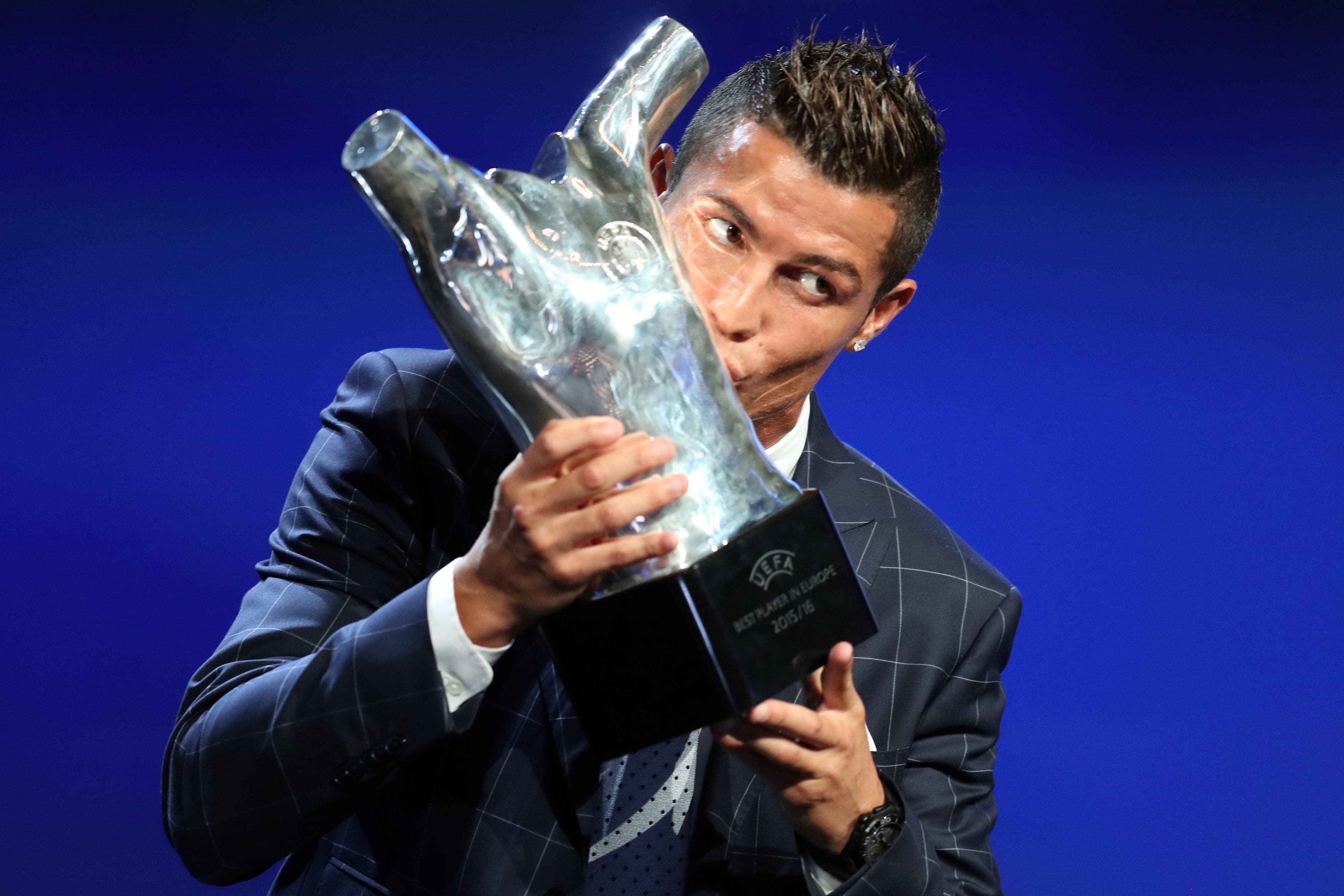 Real Madrid's Portuguese forward Cristiano Ronaldo kisses his trophy of Best Men's player in Europe at the end of the UEFA Champions League Group stage draw ceremony, on August 25, 2016 in Monaco. AFP PHOTO / VALERY HACHE