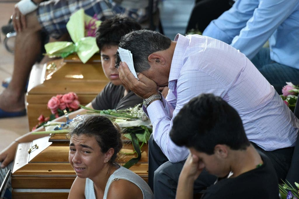 Relatives mourn next to a coffin during a funeral service for victims of the earthquake, at a gymnasium arranged in a chapel of rest on August 27, 2016, in Ascoli Piceno, three days after a 6.2-magnitude earthquake struck the region killing some 281 people. Italy prepared for an emotional day of mourning on August 27, 2016 with flags across the country to fly at half mast in honour of the 281 victims of a devastating earthquake. Grieving families began burying their dead on August 26 as rescue workers combing the rubble said they had found no new survivors in the remote mountain villages in central Italy blitzed by August 24's powerful pre-dawn quake. / AFP / ALBERTO PIZZOLI