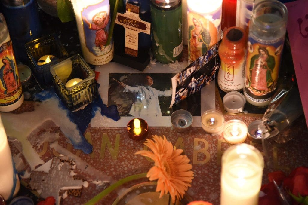 Flowers and other memoriablia are seen in the early morning hours on August 29, 2016 at the Hollywood Walk of Fame star of legendary Mexican singer and producer Juan Gabriel who died at the age of 66 after a heart attack on Sunday in Santa Monica, California. Legendary Mexican singer and producer Juan Gabriel died after a heart attack in Santa Monica, the Televisa network reported in his home country. He was 66. / AFP / Robyn BECK