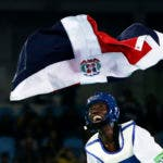Luisito Pie of the Dominican Republic celebrates with his national flag after winning a men's Taekwondo bronze medal final at the 2016 Summer Olympics in Rio de Janeiro, Brazil, Wednesday, Aug. 17, 2016. (AP Photo/Andrew Medichini)