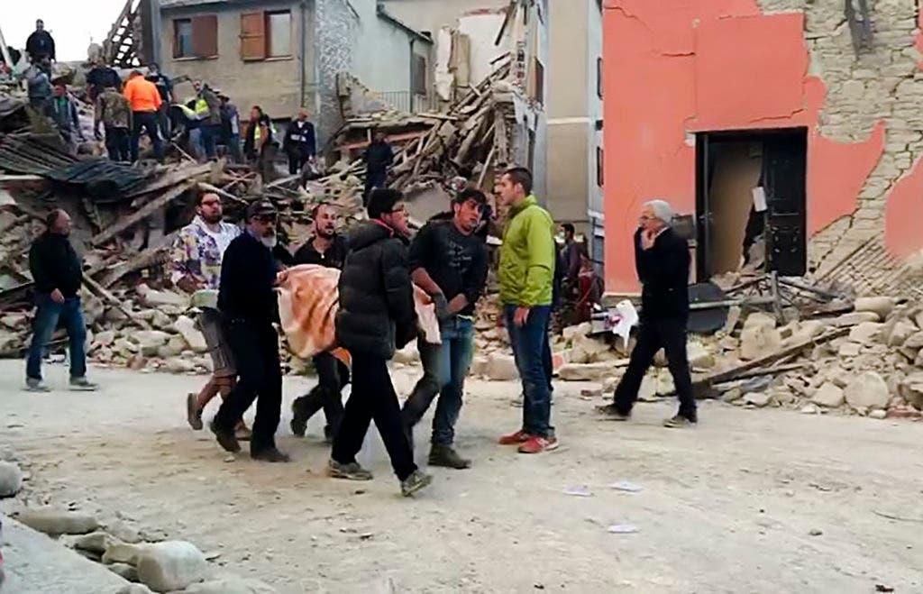En esta imagen, tomada de un video, personas recuperan a una víctima de debajo de los escombros de un edificio en Amatrice, una localidad del centro de Italia sacudida por un sismo de magnitud 6,1, el 24 de agosto de 2016. (AP Foto)