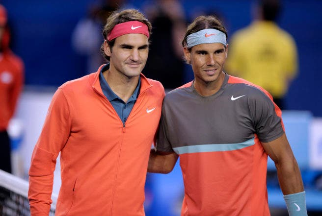 FILE - In this Jan. 24, 2014, file photo, Rafael Nadal of Spain, right, and Roger Federer of Switzerland pose at the net before their semifinal at the Australian Open tennis championship in Melbourne, Australia.Federer and Nadal say they plan to play doubles together when the Laver Cup debuts next year. (AP Photo/Rick Rycroft, File)