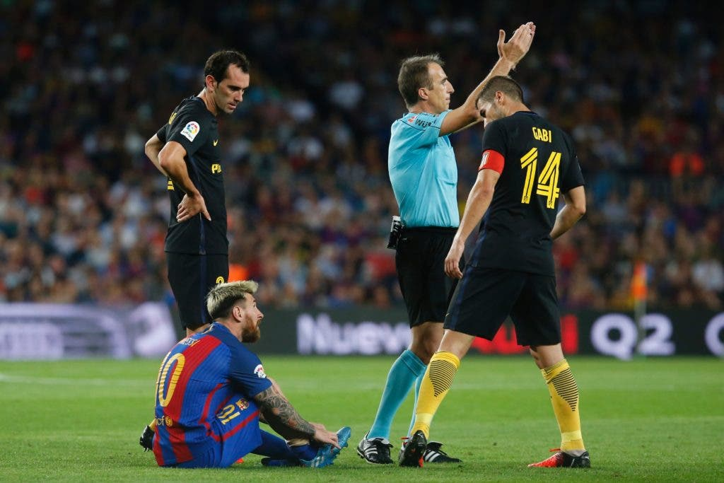 Barcelona's Argentinian forward Lionel Messi sits on the ground (L) before leaving the pitch during the Spanish league football match FC Barcelona vs Atletico de Madrid at the Camp Nou stadium in Barcelona on September 21, 2016. / AFP / PAU BARRENA