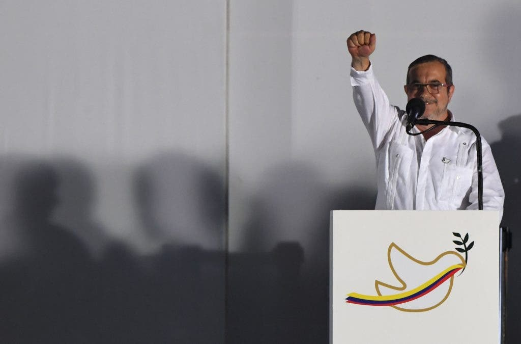 """The leader of the FARC, Rodrigo Londono (L) -- better known by his nom de guerre, Timoleon """"Timochenko"""" Jimenez delivers a speech after signing the historic peace agreement between the Colombian government and the Revolutionary Armed Forces of Colombia (FARC), in Cartagena, Colombia, on September 26, 2016  The Colombian government and the leftist FARC rebel force signed a historic peace accord to end a half-century conflict that has killed hundreds of thousands of people. Santos and """"Timochenko"""" Jimenez, signed the deal at a ceremony in the Caribbean city of Cartagena, prompting loud cheers from the crowd which included numerous international dignitaries.  / AFP / Luis ACOSTA"""
