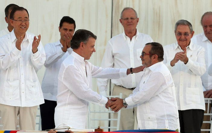 Colombia's President Juan Manuel Santos, front left, and the top commander of the Revolutionary Armed Forces of Colombia (FARC) Rodrigo Londono, known by the alias Timochenko, shake hands after signing the peace agreement between Colombia's government and the FARC to end over 50 years of conflict in Cartagena, Colombia, Monday, Sept. 26, 2016. (AP Photo/Fernando Vergara)