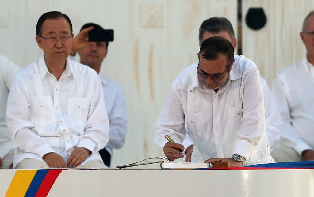 Top commander of the Revolutionary Armed Forces of Colombia (FARC) Rodrigo Londono, known by the alias Timochenko, signs the peace agreement between Colombia's government and the FARC, to end over 50 years of conflict, in Cartagena, Colombia, Monday, Sept. 26, 2016. Behind left is U.N. Secretary General Ban Ki Moon.(AP Photo/Fernando Vergara)