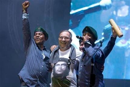 """El máximo líder de las FARC Rodrigo Londoño, también conocido como """"Timochenko"""", en el centro, es abrazado por cantantes de la banda """"Los rebeldes del sur"""" durante un concierto en la conferencia de las Fuerzas Armadas Revolucionarias de Colombia en la sabana del Yari, en el sur del país, el domingo, 18 de septiembre de 2016. Los líderes de las FARC y los delegados se reúnen para debatir y votar el acuerdo alcanzado el mes pasado con el gobierno de Colombia para poner fin a cinco décadas de guerra. (AP Foto/Ricardo Mazalan)"""