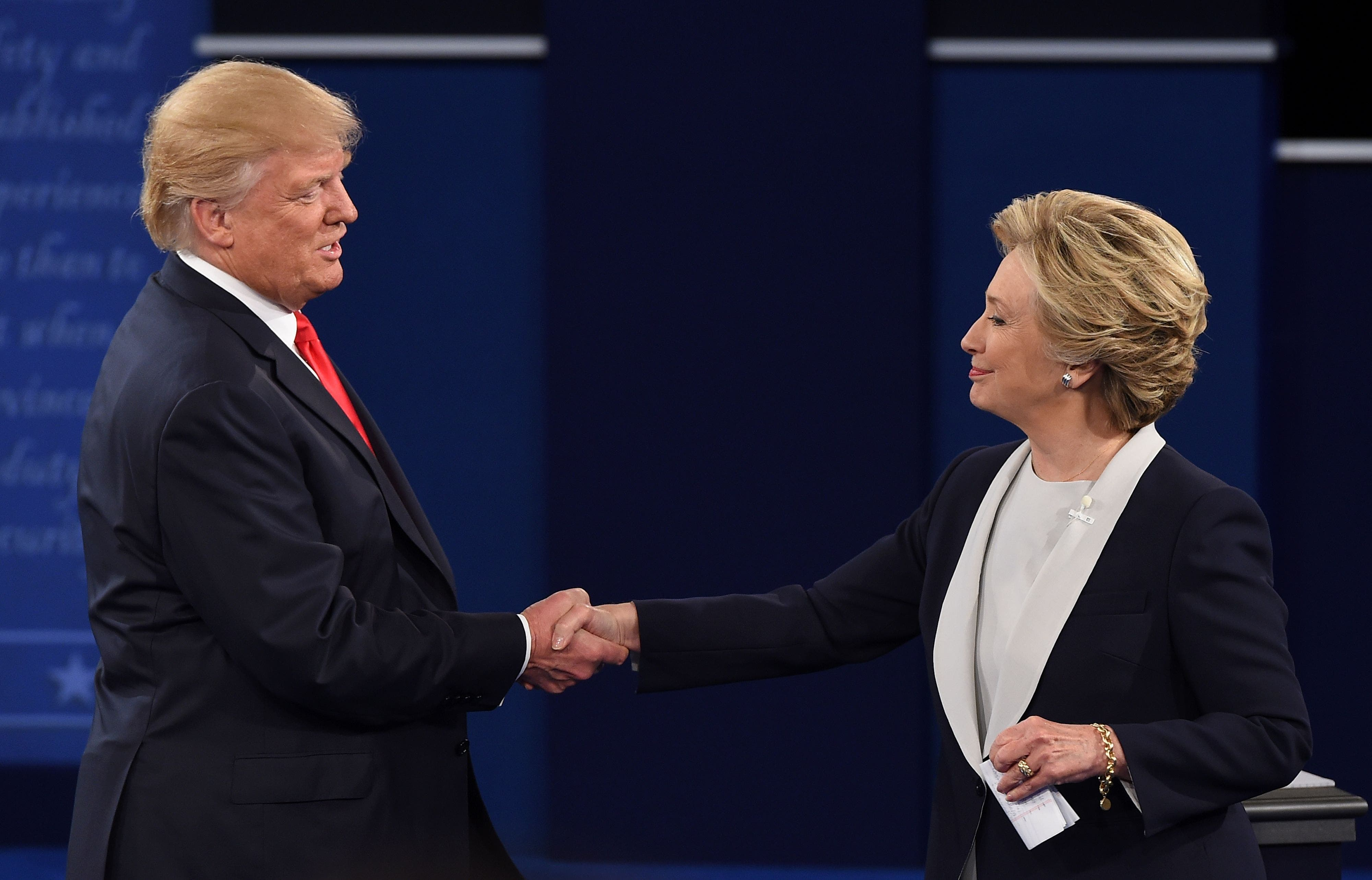 US Democratic presidential candidate Hillary Clinton and US Republican presidential candidate Donald Trump shakes hands after the second presidential debate at Washington University in St. Louis, Missouri, on October 9, 2016. / AFP / Robyn Beck