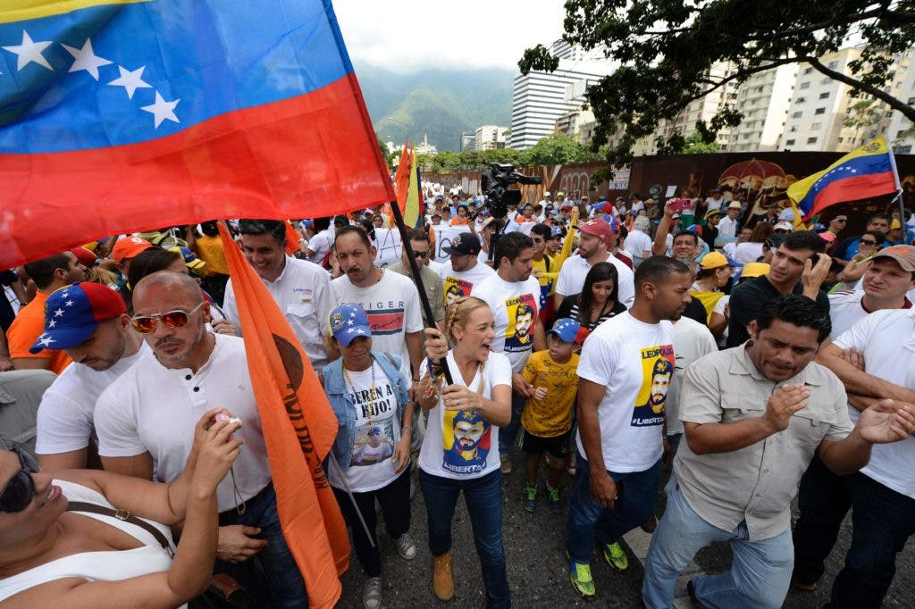 """Lilian Tintori, wife of prominent jailed opposition leader Leopoldo Lopez, waves a Venezuelan national flag as she marches against the government of President Nicolas Maduro in the streets of Caracas on October 26, 2016.  Venezuela's political rivals are set to engage in a volatile test of strength on Wednesday, with the opposition vowing mass street protests as President Nicolas Maduro resists efforts to drive him from power. The socialist president and center-right-dominated opposition accuse each other of mounting a """"coup"""" in a volatile country rich in oil but short of food. / AFP / Federico PARRA"""