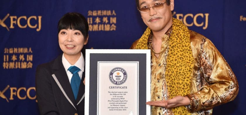 Japanese comedian Pikotaro (R) shows a Guinness World Records certificate during a press conference at the Foreign Correspondents' Club of Japan in Tokyo on October 28, 2016. A Japanese comedian's nonsense tune that became an internet sensation after Justin Bieber recommended it has entered the Guinness World Records as the shortest song to break into the Billboard Hot 100. / AFP / KAZUHIRO NOGI