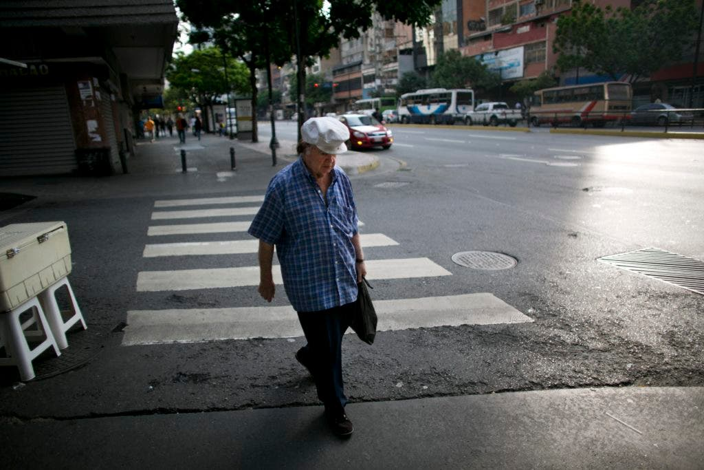 A man walks along on a street in Caracas, Venezuela, Friday, Oct. 29, 2016. Some stores and schools are closed and rush-hour traffic noticeably lighter as many residents in the capital have stayed home to express their opposition to President Nicolas Maduro as part of a 12-hour work stoppage after authorities canceled a recall referendum seeking his removal. (AP Photo/Ariana Cubillos)