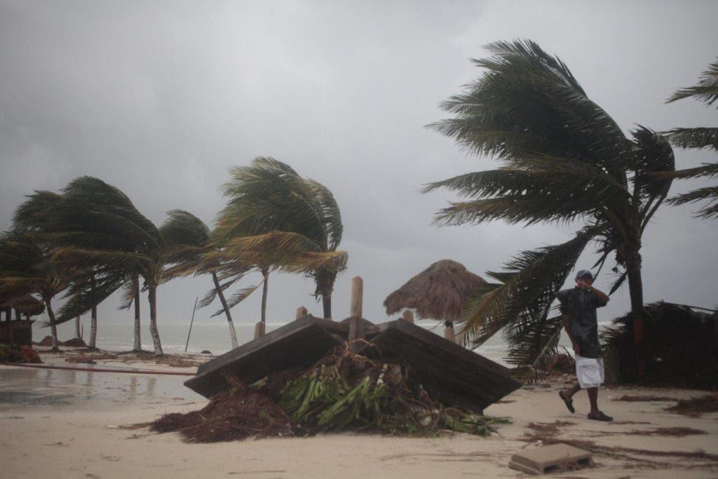 """MEX18. MAJAHUAL (MÉXICO), 08/08/2012.- Un hombre camina entre los destrozos causados por """"Ernesto"""" hoy, miércoles 8 de agosto de 2012, luego del paso de la tormenta tropical por el puerto turístico de Mahahual (México). """"Ernesto"""" sigue perdiendo intensidad en territorio mexicano al bajar sus vientos máximos sostenidos a 75 kilómetros por hora, pero es posible que se fortalezca cuando se desplace por la bahía de Campeche. EFE/STR"""
