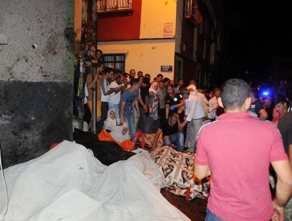 People react after an explosion in Gaziantep, southeastern Turkey, early Sunday, Aug. 21, 2016. Gaziantep Province Gov. Ali Yerlikaya said the deadly blast, during a wedding near the border with Syria, was a terror attack. (Eyyup Burun/DHA via AP)