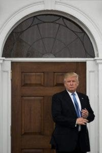 BEDMINSTER TOWNSHIP, NJ - NOVEMBER 20: President-elect Donald Trump stands outside the clubhouse following his meeting with Peter Kirsanow, attorney and member of the U.S. Commission on Civil Rights, at Trump International Golf Club, November 20, 2016 in Bedminster Township, New Jersey. Trump and his transition team are in the process of filling cabinet and other high level positions for the new administration.   Drew Angerer/Getty Images/AFP == FOR NEWSPAPERS, INTERNET, TELCOS & TELEVISION USE ONLY ==