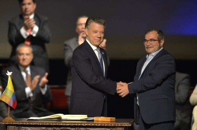 Colombian President Juan Manuel Santos (L) and the head of the FARC guerrilla Timoleon Jimenez, aka Timochenko, shake hands during the second signing of the historic peace agreement between the Colombian government and the Revolutionary Armed Forces of Colombia (FARC), at the Colon Theater in Bogota, Colombia, on November 24, 2016.  Under pressure for fear that a fragile ceasefire could break down, the government and the Revolutionary Armed Forces of Colombia (FARC) sign the new deal and immediately take it to Congress. The plan bypasses a vote by the Colombian people after they unexpectedly rejected the first version of the deal in a referendum last month. The accord aims to end Latin America's last major armed conflict. But opponents say it is too soft on the leftist FARC force, blamed for many thousands of killings and kidnappings.  / AFP / LUIS ROBAYO