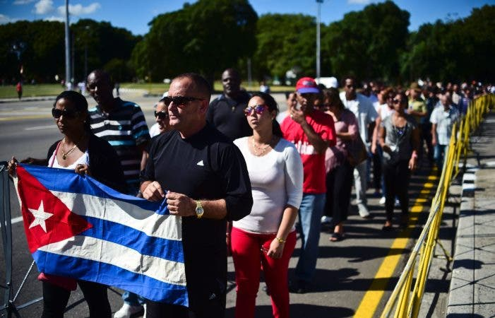 People holding a Cuban national flag queue to enter Jose Marti's memorial to pay their last respects to Cuban revolutionary icon Fidel Castro at Revolution Square in Havana, on November 28, 2016.  A titan of the 20th century who beat the odds to endure into the 21st, Castro died late Friday after surviving 11 US administrations and hundreds of assassination attempts. No cause of death was given. Castro's ashes will go on a four-day island-wide procession starting Wednesday before being buried in the southeastern city of Santiago de Cuba on December 4. / AFP / RONALDO SCHEMIDT